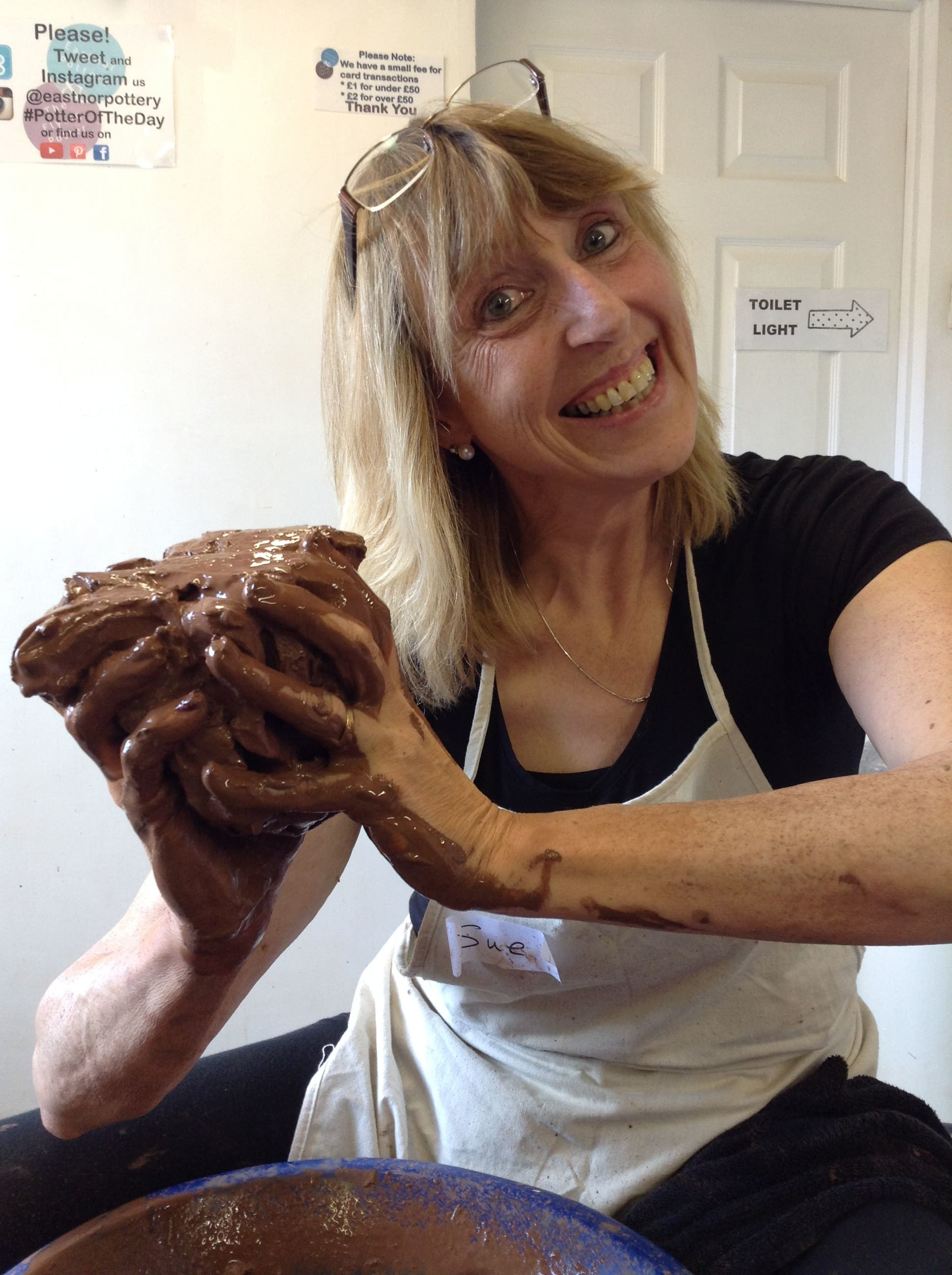 A lady holding clay as she makes a pot on the otter's wheel one day course