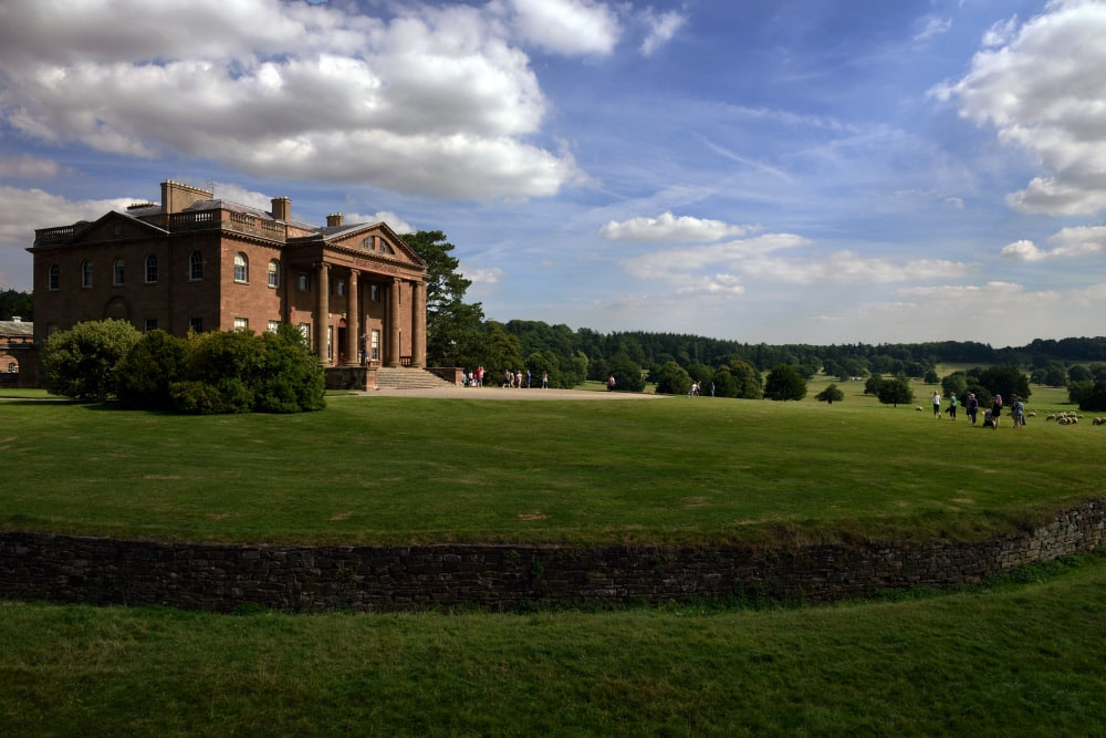 Visitors walking in the gardens, near the Ha-ha with the West Face of the house in the background. Berrington Hall, Herefordshire.