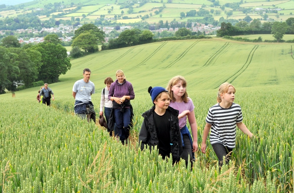 A picture of walkers Walking the Wyche Way with Kington in the background.